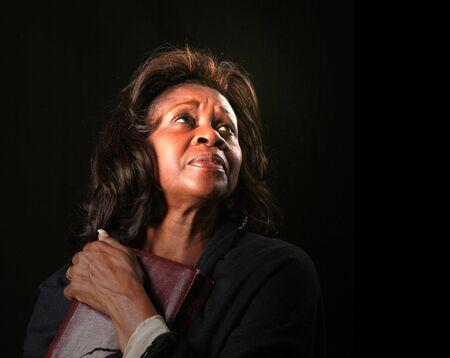 A spiritual black woman clutching her bible and looking toward heaven photo