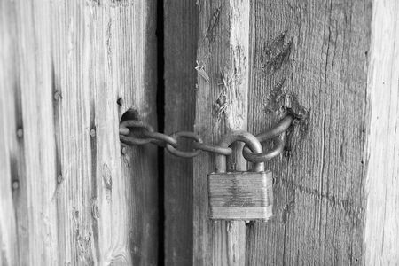 barn black and white: An old lock on a barn door in black and white