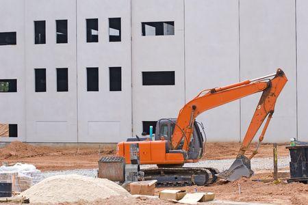 front end loader: An orange front end loader at construction site with sand pile