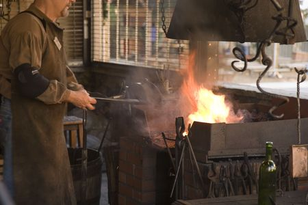 forge: A blacksmith working at an old iron forge Stock Photo