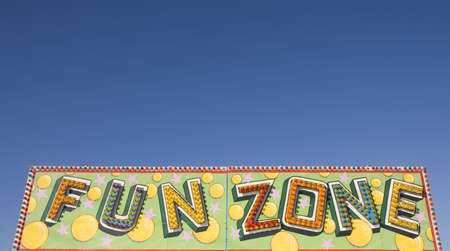 A colorful fun zone sign at a carnival against a blue sky