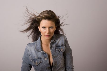 A young fresh fashion model with wind blown hair photo