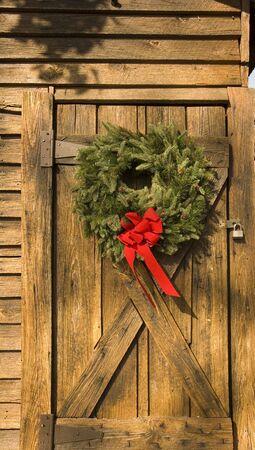 A Christmas krans op een oude schuur deur Stockfoto