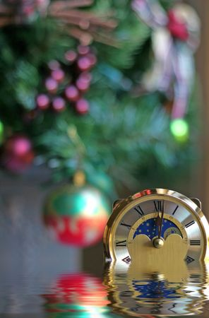 past midnight: Anniversary clock at one minute past midnight with Christmas tree in background with water effect in foreground Stock Photo