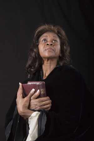 A black woman clutching her bible and looking toward heaven