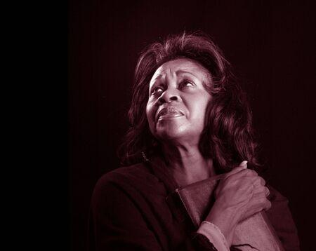 A spiritual black woman clutching her bible photo