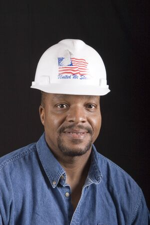 A smiling black man in denim shirt and hard hat