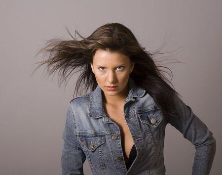 A fresh brunette fashion model in denim jacket unbuttoned