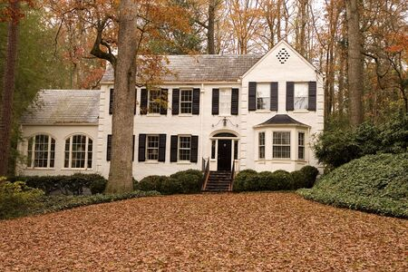 A nice white two story house with leaves covering the lawn Stock Photo - 2207546