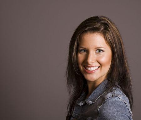 A brunette fashion model in denim jacket smiling against a grey background