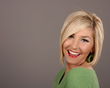 A fresh young blonde model smiling at camera on grey background