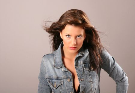 A beautiful brunette fashion model in denim jacket unbuttoned and hair blowing in the wind Фото со стока