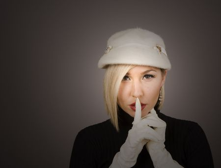 A blonde model in white hat and gloves with spotlight on face