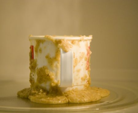 A cup running over with hot oatmeal in a microwave oven