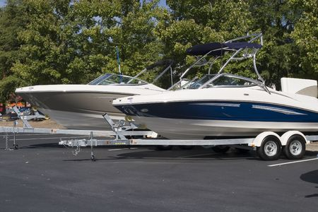 Two luxury ski or fishing boats on trailers in a parking lot