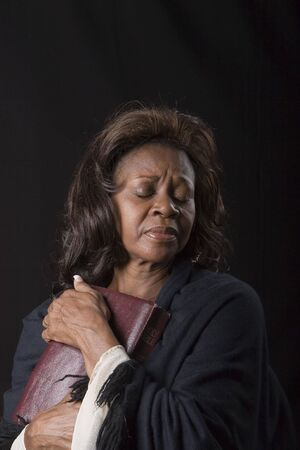 A black woman in robes clutching a bible with eyes closed as in prayer or reverence