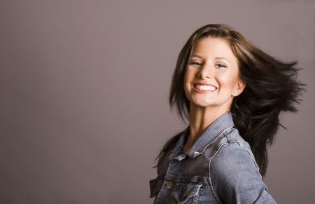A brunette model in denim jacket flipping hair photo