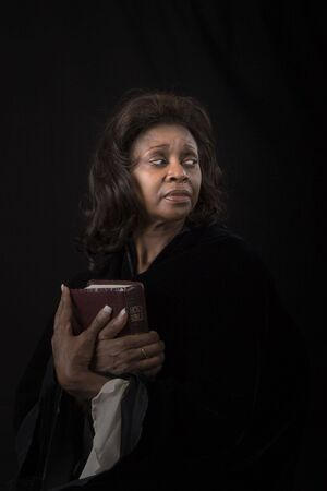A woman holding a bible to her chest and looking to the left on black background