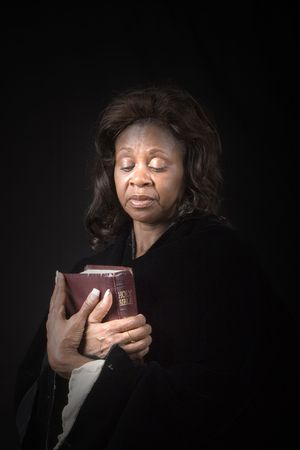 A black woman holding a bible and looking at it in reverence photo