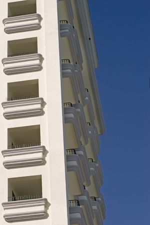 Balconies on a high rise tropical deluxe hotel against blue sky