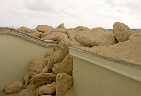 A concrete wall broken by beach sand washed in by a hurricane Stock Photo