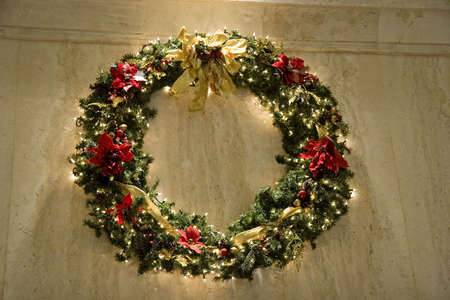 A brightly decorated christmas wreath hanging on a marble wall