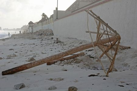 A thatched umbrella knocked down and stripped of straw against a wall after a storm
