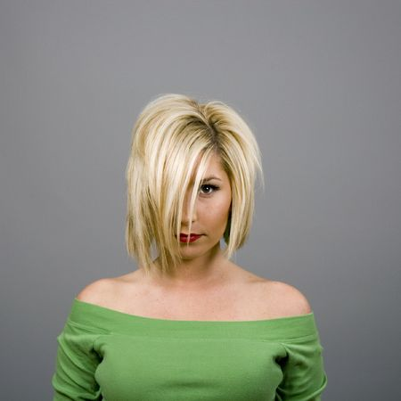 A blonde fashion model in green blouse with hair over her face against a grey background photo