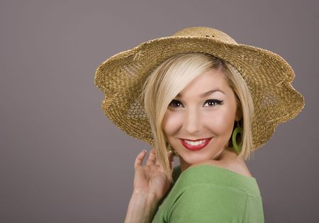 A blonde model in a green blouse and a straw hat smiling at the camera photo