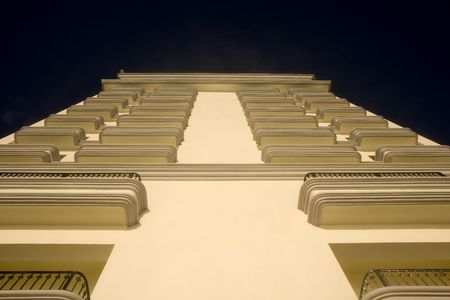 A white building from below with balconies into the blue sky