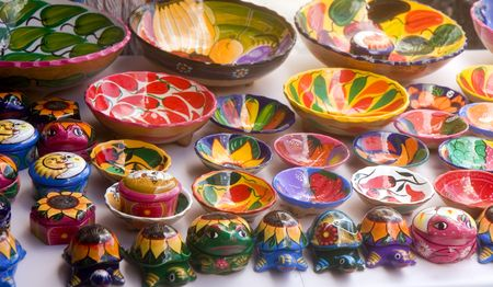 crafts: A display of colorful pottery and figurines at a Mexican flea market