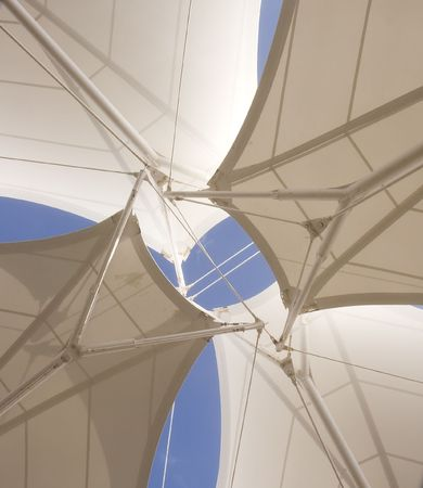 A roof made of layers of white vinyl stretched under a blue sky