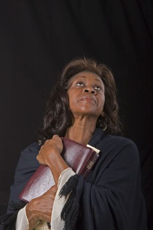 woman hands up: A spiritual black woman in a black robe holding a bible and looking toward heaven