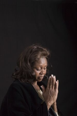 A black woman in low key lighting bowing her head in prayer