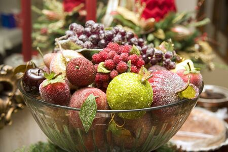 A bowl of brightly decorated fake fruit on a buffet set for Christmas photo