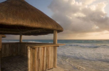 dawns: A straw and bamboo beach hut against the sea in the dawns early light