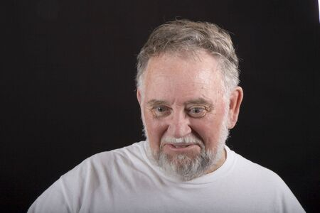An older man in white tshirt on a black background looking down with an expressive face Stock Photo - 2456754