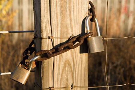 Old rusty locks and a chain on a wire and post fence Stock Photo - 2465731