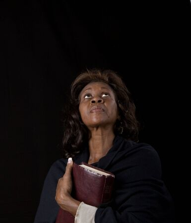 A black woman clutching a bible to her chest and looking toward heaven photo