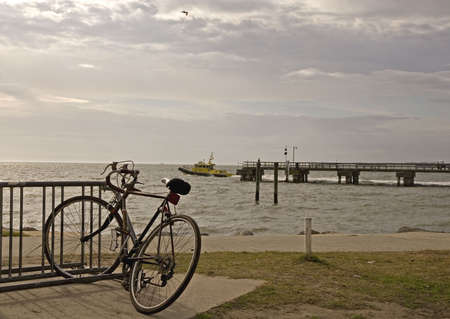 A bicycle on a rack with a pier and a pilot boat in the background photo
