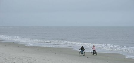 Two people riding bicycles alone on a winter beach photo