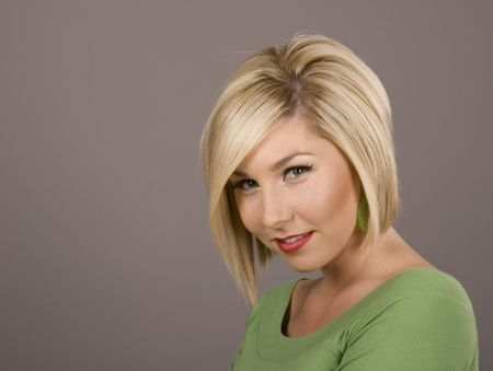 A blonde model in green blouse, her head down with a smirk on\ her face.