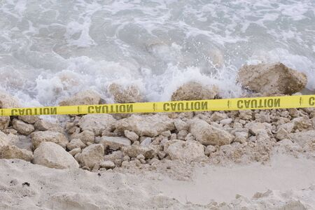 Major beach erosion making it dangerous to use. Yellow caution tape has been strung in place
