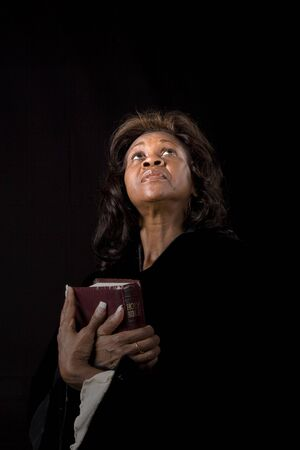 A black woman holding a bible looking toward heaven with her face illuminated by spot Imagens