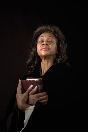 A black woman holding a bible and closing her eyes in prayer photo