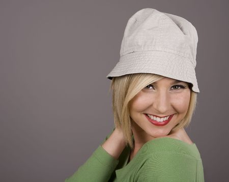 A blonde in a green blouse and silly white hat smiling with her hand behind her head Stock Photo - 2626186