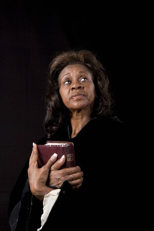 A black woman holding a bible and bright eyes turned to heaven photo