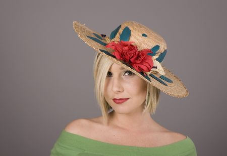 flowered: A blonde in a flowered straw hat pulled low over one eye Stock Photo
