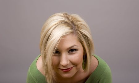 head bowed: A blonde girl in a green blouse with her head bowed smiling at camera