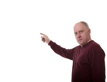 A man in  a red shirt pointing at copy space and looking toward camera Фото со стока